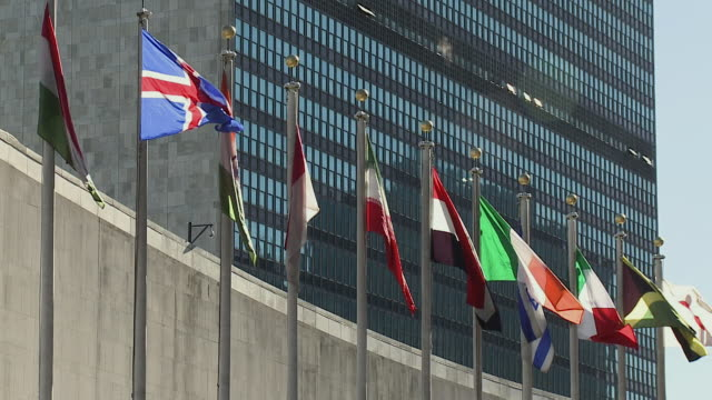 row of flags flapping in wind in front of united nations building / new york city new york usa - united nations stock-videos und b-roll-filmmaterial