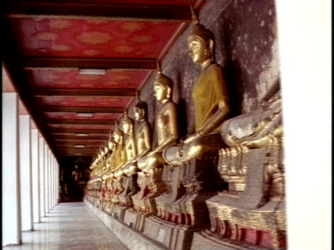 ms, pan, row of gold colored buddha statues lining wall in temple hallway, wat mahathat, bangkok, thailand - männliche figur stock-videos und b-roll-filmmaterial