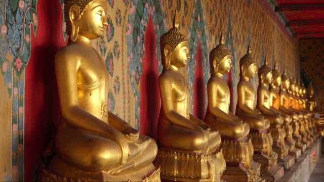 row of golden buddha statues at wat arun temple in bangkok, thailand - buddha stock-videos und b-roll-filmmaterial
