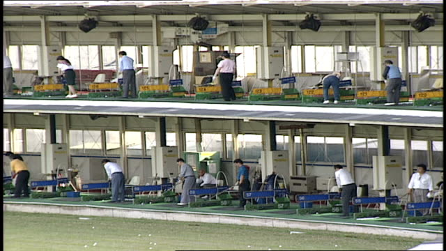 row of golfers at driving range in tokyo - driving range stock videos & royalty-free footage