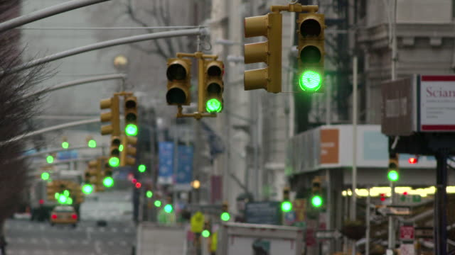 A row of green lights turn from green to yellow then red on a empty New York City Street on a cloudy morning.