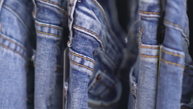 row of hanged blue jeans,dolly shot - industry stock videos & royalty-free footage