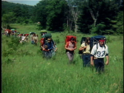 1976 WS COMPOSITE Row of hikers crossing field, Vermont, USA