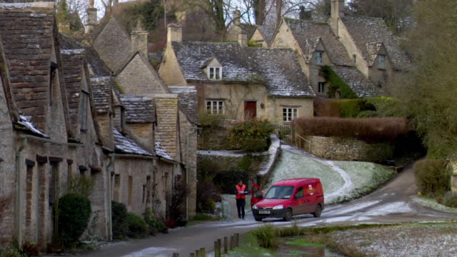ws row of houses and red van, postman delivering letters / arlington row, bibury, uk - mail stock videos and b-roll footage