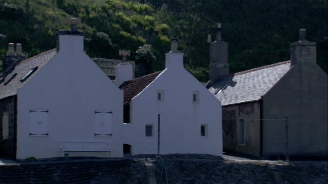 a row of houses are built along the hillside of crovie scotland. available in hd. - クロヴィー点の映像素材/bロール