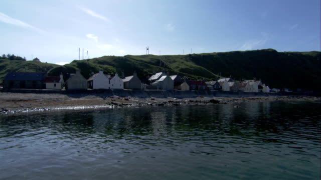 a row of houses are built along the rocky shores of crovie scotland. available in hd. - クロヴィー点の映像素材/bロール