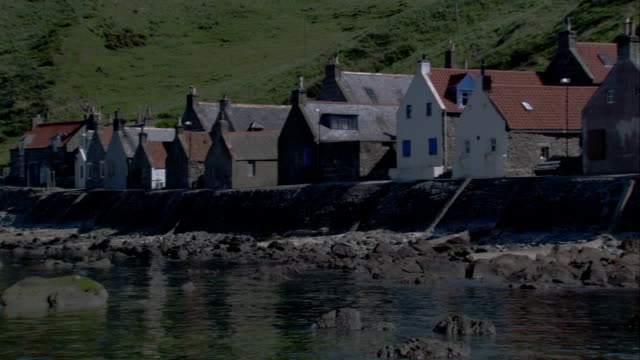 a row of houses are built on the rocky shores of crovie scotland. available in hd. - クロヴィー点の映像素材/bロール