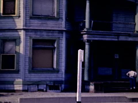 row of houses in poor neighborhood, kids play on stoop. los angeles slum on january 01, 1950 in los angeles, california - slum stock videos & royalty-free footage