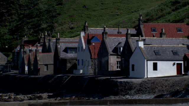 a row of houses is built along the hillside of crovie scotland. available in hd. - クロヴィー点の映像素材/bロール
