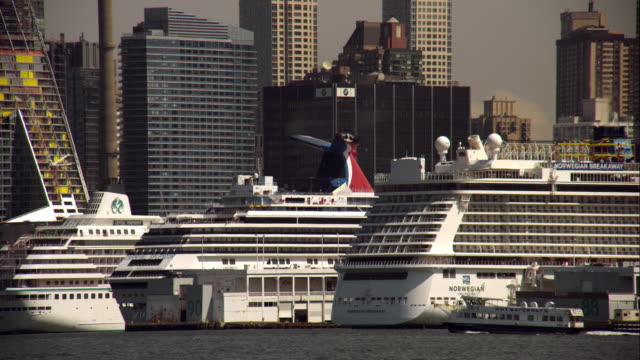 row of large cruise liners in anchored port as small ferry passes by - anchored stock videos & royalty-free footage