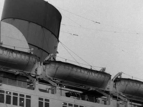 A row of lifeboats are fastened to the top deck of the Queen Mary ocean liner