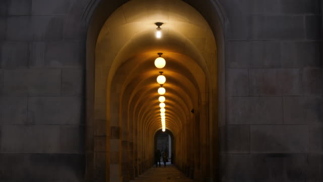 A row of lights illuminate an arched passageway at dusk