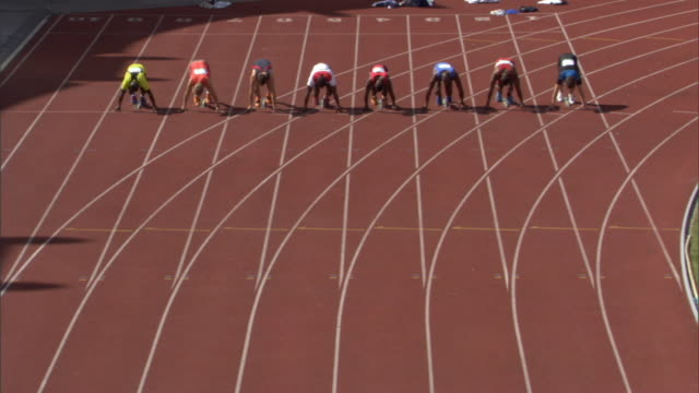 ha ws row of men crouching in starting position on sports track/ men running as race starts/ sheffield, england - 耐久力点の映像素材/bロール