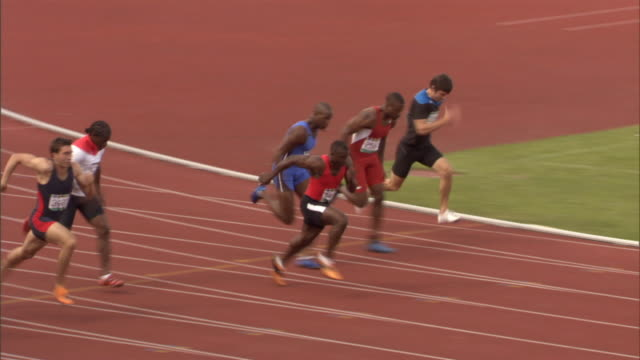 stockvideo's en b-roll-footage met ha ws row of men crouching in starting position on sports track/ men running as race starts/ winner putting arms up as he crosses finish line/ sheffield, england - beëindigen