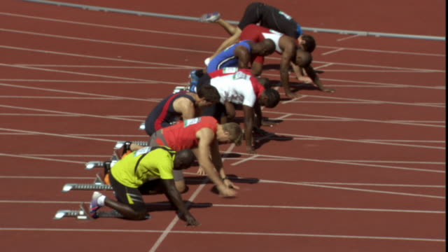 ha ws row of men crouching in starting position on sports track/ men running as race starts/ sheffield, england - しゃがむ点の映像素材/bロール