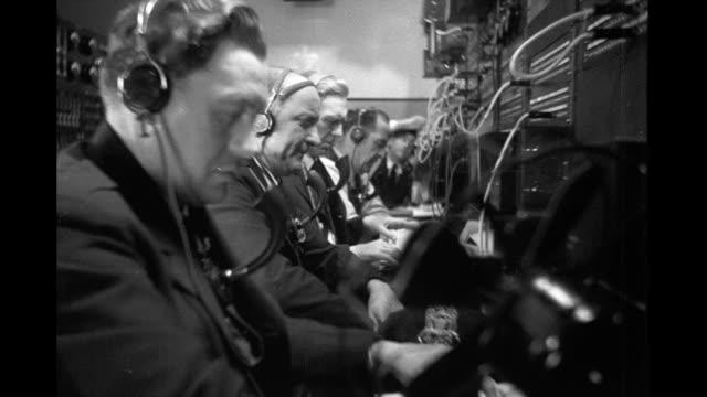 vídeos de stock, filmes e b-roll de row of men police dispatchers operating switchboard row of men operating switchboard on january 01 1930 - fone de ouvido equipamento de som