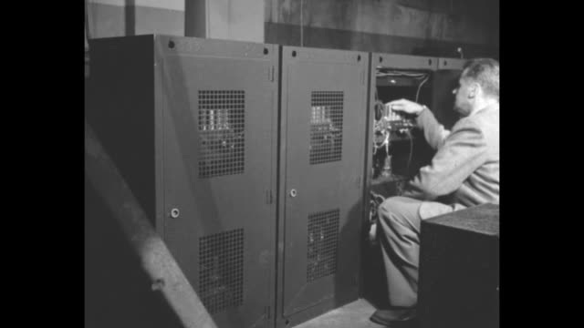 VS row of metal cabinets with man in suit adjusting electrical components and turning dials on control panel as carillon is installed