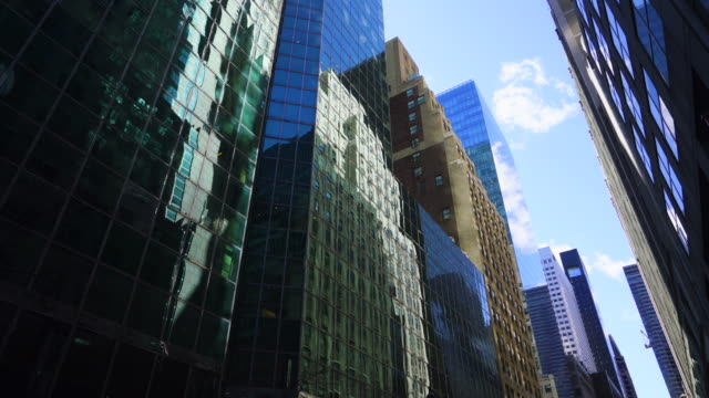 Row of Midtown Manhattan office buildings along both side of street in New York City. Building surface reflects figure of the other buildings.