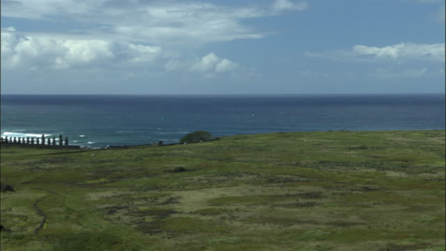 ws pan row of moai statues along coastline / easter island, chile - horizon over water stock-videos und b-roll-filmmaterial