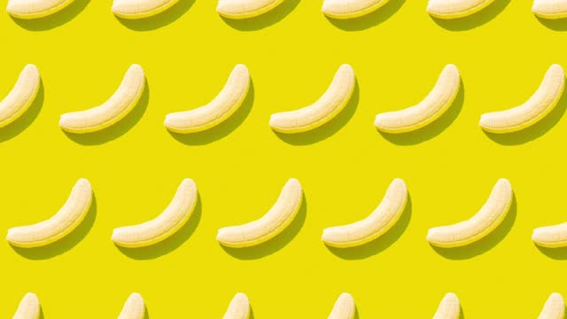 row of moving peeled bananas on yellow background - yellow stock videos & royalty-free footage