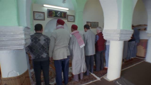 ms, pan, row of muslim men praying, rear view, small mosque, kairouan, tunisia - kufi stock videos & royalty-free footage