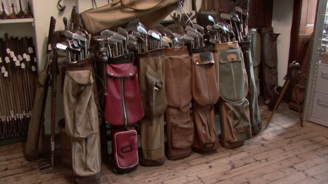 ha row of old golf bags full of golf clubs / st. andrews, scotland, united kingdom - golf bag stock videos & royalty-free footage