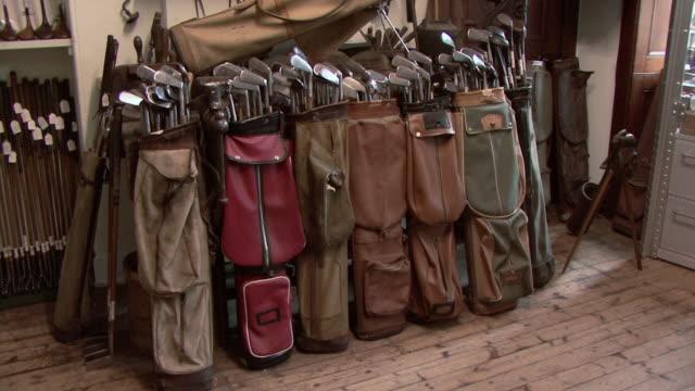 vídeos de stock, filmes e b-roll de ha row of old golf bags full of golf clubs / st. andrews, scotland, united kingdom - bolsa de golfe