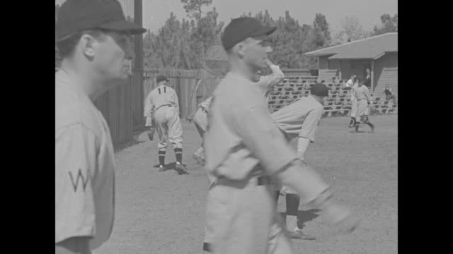 row of players talking while posing for photo opportunity / row of players throwing and catching / players throwing catching batting / manager joe... - spring training stock videos & royalty-free footage