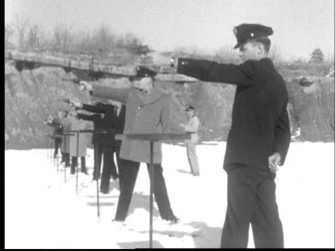 1956 MS Row of police officers firing hand guns at snowy shooting range/ PAN to targets/ Lansing, Michigan