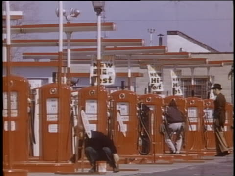 1958 row of red gas pumps + men working at gas station - filling station attendant stock videos & royalty-free footage
