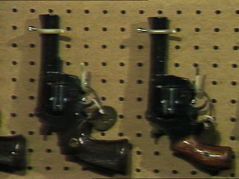 row of revolvers attached to pegboard; different sizes and models. black rifles lined up and stored on a wooden gun rack vertically; adult caucasian... - gun stock videos & royalty-free footage