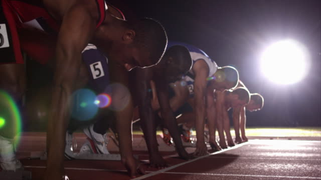 A row of runners crouch in the starting position before beginning to race.