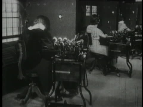 b/w 1930 row of secretaries using early telephone technology - 1930 stock-videos und b-roll-filmmaterial