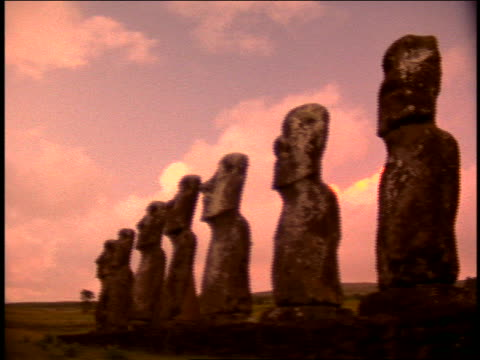 PINK SILHOUETTE row of seven stone statues (moai) of Ahu Akivi on terraced hill / Easter Island