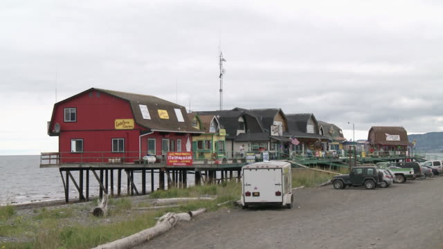 """row of shops/businesses on raised boardwalk, car park in front, homer spit, homer, kenai peninsula, alaska."" - kenai stock videos & royalty-free footage"
