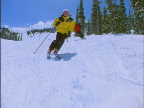 vídeos de stock e filmes b-roll de row of skiers skiing downhill - bastão de esqui