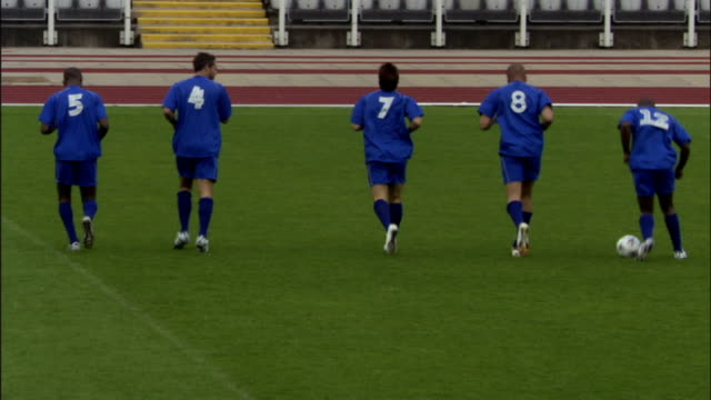 ws zi row of soccer players in blue uniforms running in a row and dribbling ball during practice/ sheffield, england - shoes in a row stock videos & royalty-free footage