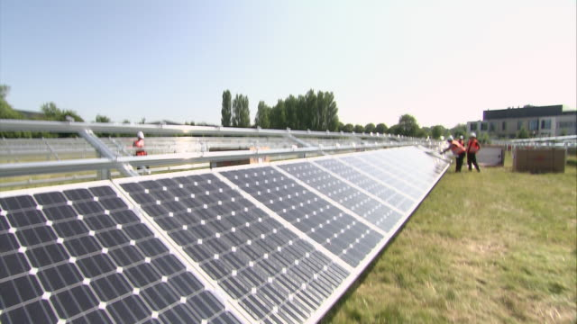 vídeos de stock e filmes b-roll de ws td row of solar panels being installed and three models working in distance / howbery, oxfordshire, united kingdom - painel solar