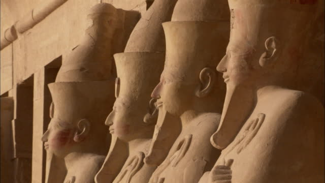 a row of statues of hatshepsut stand outside a temple. available in hd. - hatschepsut tempel stock-videos und b-roll-filmmaterial