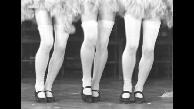 VS row of stockinged chorus line legs dancing / Pan up legs to reveal that the dancers are all men in tutus and stockings / CU man in blond wig...