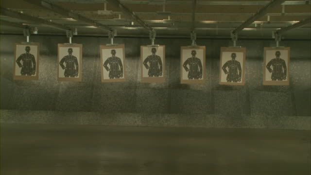 vidéos et rushes de a row of targets with bullet holes moves forward in a shooting range. - tir à l'arme à feu