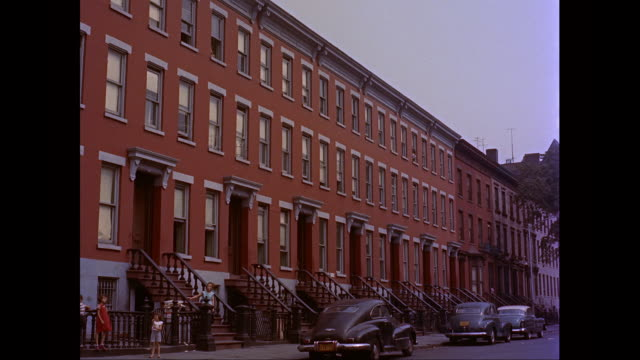 ms row of tenement/residential buildings, cars parked on street, people / new york city, new york state, united states  - 1955年点の映像素材/bロール