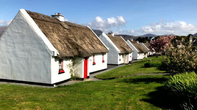 Row of thatched roof cottages in a street in Ireland near Galway
