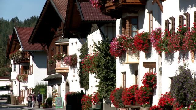 row of traditional houses with flower boxes in full bloom - window box stock videos & royalty-free footage