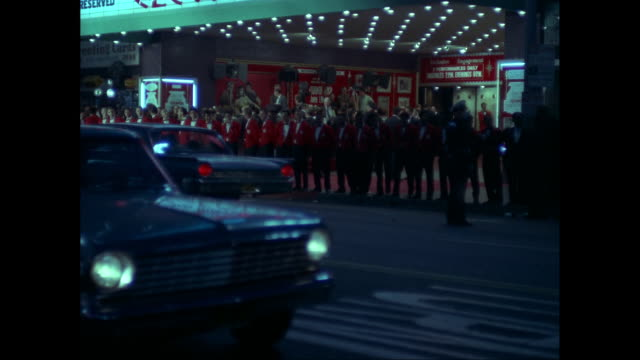 ws row of ushers in red jackets standing outside pantages theatre at night, traffic in foreground / los angeles, california, united states - theater marquee commercial sign stock videos & royalty-free footage