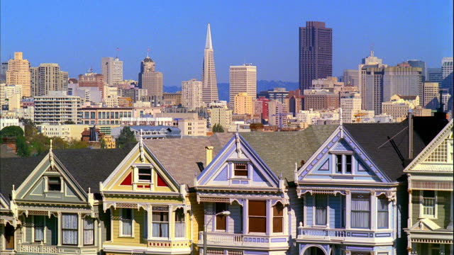 vídeos y material grabado en eventos de stock de ms, row of victorian houses at alamo square park with city skyline in background, san francisco, california, usa - pirámide transamerica san francisco