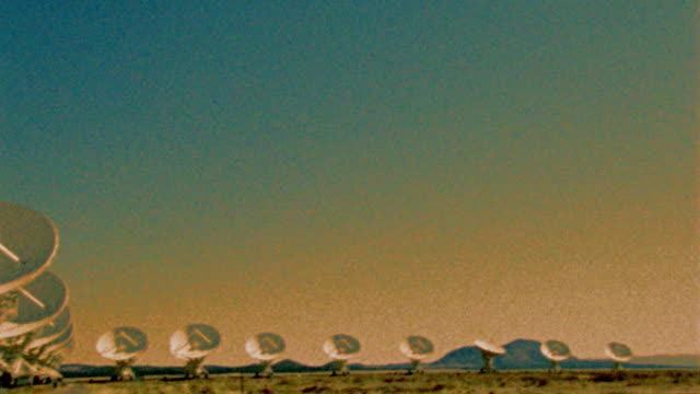 grainy pan row of vla (very large array) radio telescope dishes in desert / new mexico - 1999 stock videos & royalty-free footage