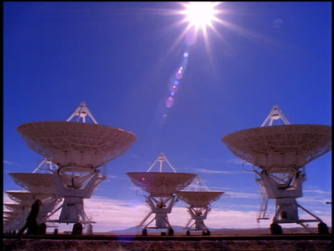 stockvideo's en b-roll-footage met row of vla radio telescope dishes with businessman on cell phone walking in foreground / new mexico - astronomietelescoop