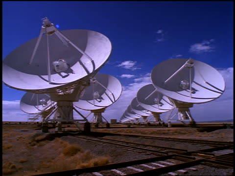 Row of VLA radio telescope dishes with businessman on cell phone walking on tracks in foreground / New Mexico