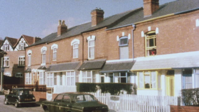 1983 montage row of well maintained terraced homes and resident crossing her home using a walker / united kingdom - row house stock videos and b-roll footage